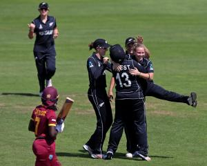 Leigh Kasperek of New Zealand celebrates with teammates after taking the wicket of Stafanie...