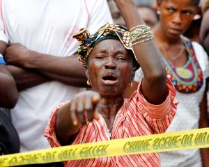 The mother of a mudslide victim grieves near the entrance of Connaught Hospital in Freetown,...