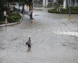 A man walks through a flooded street as Typhoon Hato hits Hong Kong. Photo Reuters