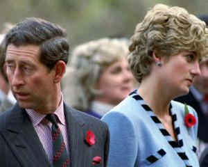 Britain's Princess Diana and Prince Charles look in different directions during a Korean War...