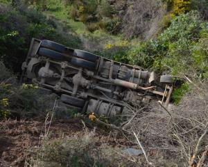 The truck lies down the bank after coming off the road near Portobello. Photo Gerard O'Brien