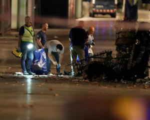 Forensic police officers search for clues near the area where a van crashed into pedestrians at...