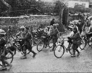 British soldiers from a cycle unit give French children a ride on their bicycles as they pass...