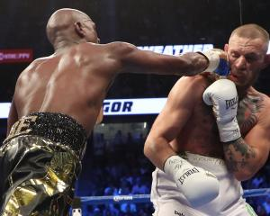 ) Floyd Mayweather Jr. throws a punch at Conor McGregor during their super welterweight boxing...