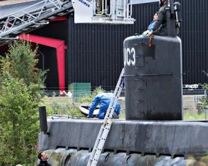 "Police technicians investigate the rescued private submarine ""UC3 Nautilus"" in Copenhagen. Photo:..."