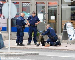 The suspect lies on the ground surrounded by police officers at the Market Square where several...