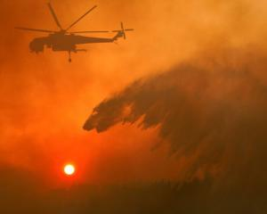 A firefighting helicopter makes water drop as a wildfire burns near the village of Metochi. Photo...