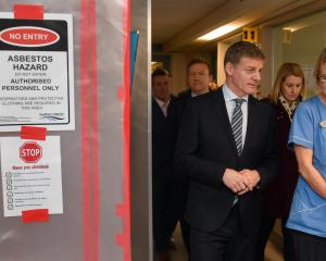 Prime Minister Bill English and Dunedin Hospital charge nurse Mary Molloy walk past a sign...