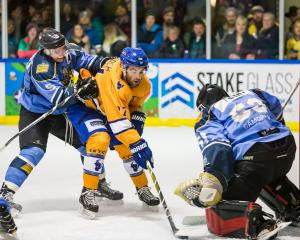 Stampede's Colin McIntosh (centre) has his eyes on the prize during the New Zealand Ice Hockey...