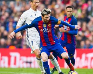 Barcelona's Lionel Messi controls the ball as Real Madrid's Cristiano Ronaldo follows him closely...