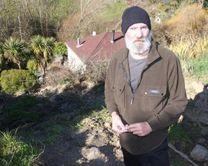 Oamaru man Gordon Stringer stands on what used to be a bank before it slipped and part of it...
