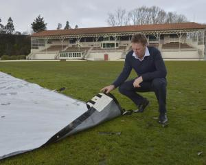 Otago Cricket Association Mike Coggan inspects the wicket block at the University Oval yesterday....