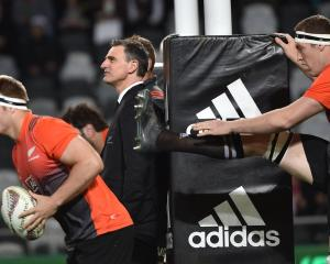 Scott McLeod stands beside the posts at Forsyth Barr Stadium last week while All Blacks Sam Cane ...