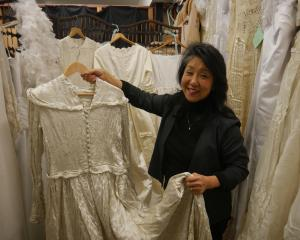 Shop on Carroll manager Fiona Dodds shows off one of the dresses that has been donated to the...