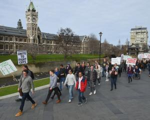 Placard-carrying University of Otago staff and students march from the University Union lawn...