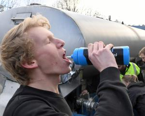 University of Otago student James Tweed drinks water from a tanker during the city's water...