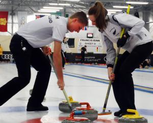 Working together to sweep their stone into the house are the New Zealand junior mixed-doubles...