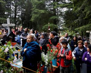 Friends and relatives attend a burial service for Maria Ortiz, one of the victims of the...