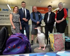 "A ""visitor'' makes an appearance on the Dunedin Airport baggage carousel watched by (from left)..."