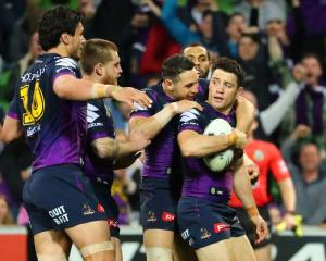 Cooper Cronk is mobbed by Melbourne Storm players after scoring a try that was later disallowed....
