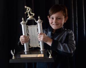 Cooper Stumbles shows off the Otago Indoor Bowls Invitational Pairs trophy he helped win. Photo:...