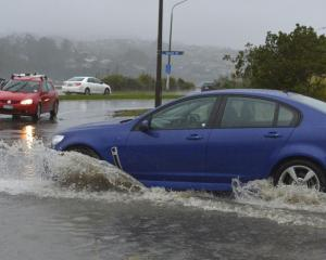 A car ploughs through floodwater on Teviot St in Dunedin during the July deluge. Photo: Gerard O...