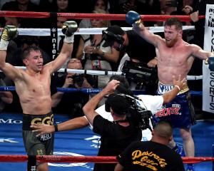 Gennady Golovkin and Canelo Alvarez both celebrate after the final round in their WBC, WBA and...