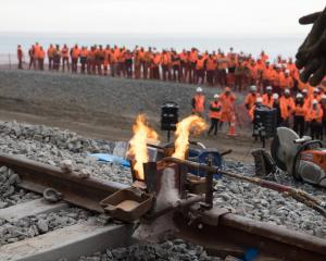 Railway workers gather north of Kaikoura, at a remote site, watching the final track-weld a...
