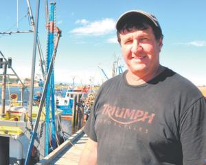 Mark Thomas with the Wendy J, in the Greymouth port in 2013. Photo: Greymouth Star