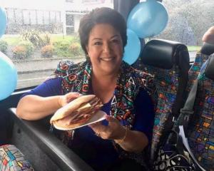 Paula shows off her panini, wearing a jacket that blends very well with the bus seats. Photo /...