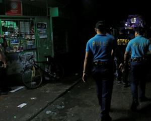 Policemen from Caloocan Police District patrol a dimly lit alley at a residential district in...
