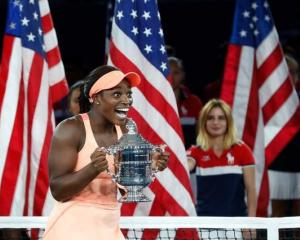 Sloane Stephens of the United States reacts with the trophy after defeating fellow American...