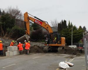 Workers remove debris blocking Lakeside Rd and install concrete blocks at the road edge. Photo:...