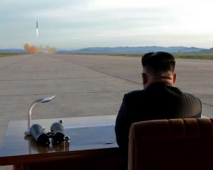North Korean leader Kim Jong Un watches the launch of a missile in this undated photo. Photo:...