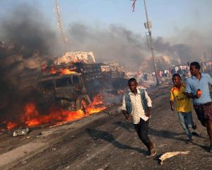 People run from the scene of one of the blasts in the Hodan district of Mogadishu. Photo Reuters