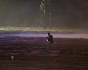 Lanny Dean, from Tulsa, Oklahoma, wades along a flooded Beach Boulevard next to Harrahs Casino as...