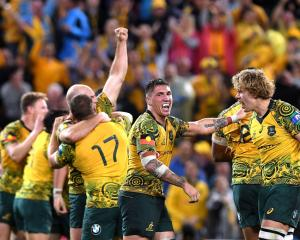 Wallabies players celebrate their win over the All Blacks. Photo Getty