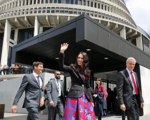 Prime Minister Jacinda Ardern, walking with partner Clarke Gayford, acknowledges the crowd...