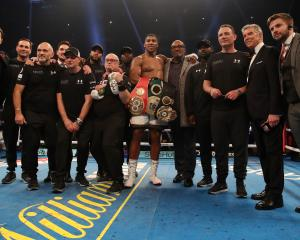 Anthony Joshua celebrates victory over Carlos Takam with his father Robert and his team after the...