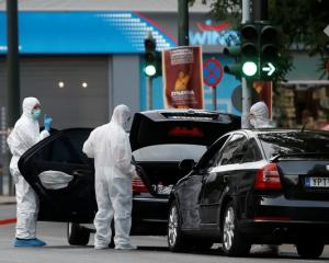 Forensics officers inspect the car of former Greek prime minister and former central bank chief...