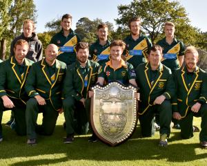 The Green Island cricket team celebrate with the Bing Harris Trophy at Logan Park in March. ...
