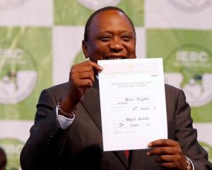 Incumbent President Uhuru Kenyatta holds the certificate of President-Elect of the Republic of...