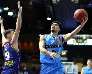 Breakers point guard Shea Ili finishes with his left hand against the Brisbane Bullets last night...