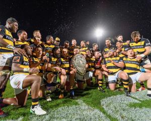 Captain Angus Ta'avao of Taranaki and his team mates pose with the Ranfurly Shield their win...