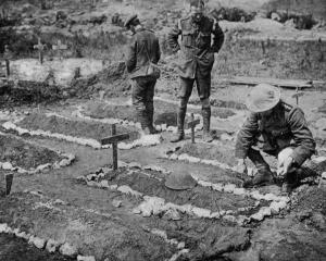 An army chaplain tending a Tommy's grave on the Western Front. — Otago Witness, 10.10.1917.
