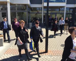 University of Otago staff leave a meeting today where they were told 160 jobs would be cut. Photo...