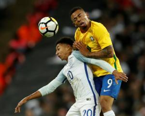 Brazil's Gabriel Jesus (R) vies for the ball with England's Jesse Lingard. Photo: Reuters