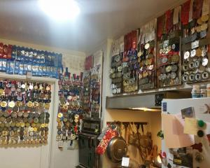 All the medals won by swimmer Craig Walker at Masters Games events around the world hang in his...