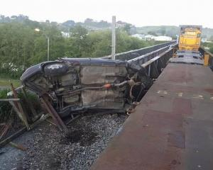 A stolen car was destroyed after it was hit by a train on the Aramoho Rail Bridge. Photo: NZ Herald