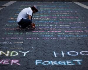 Street artist Panzarino prepares a memorial as he writes the names of the Sandy Hook Elementary...